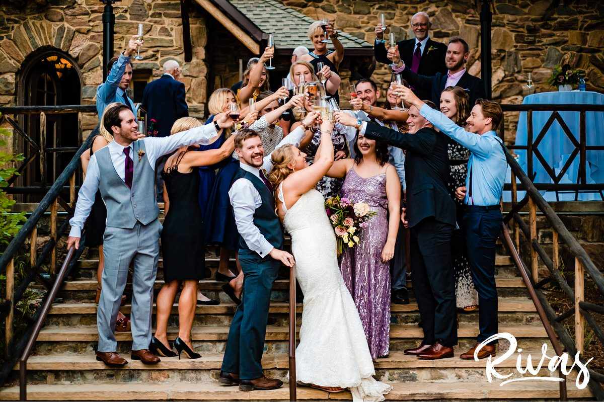 8 Things Your Wedding Photographer Wants you to Know | A group photo of a bride and groom toasting with champagne just after their wedding ceremony celebration.