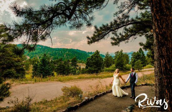 Chief Hosa Lodge Wedding Sneak Peek | Wedding couple walks holding hands down a path in the mountains