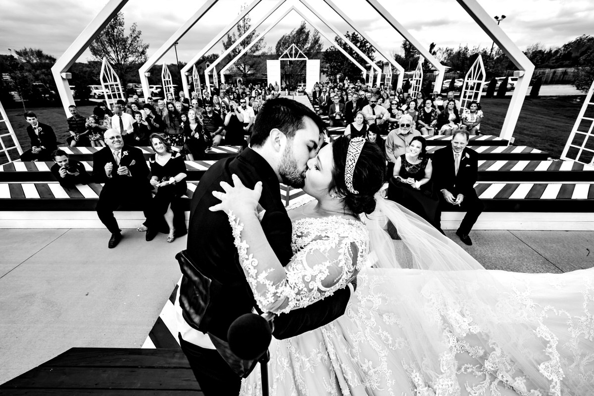 A candid, black and white picture taken from behind the bride and groom, looking out at their audience as they share their first kiss on their wedding day at The Pavilion in Kansas City.