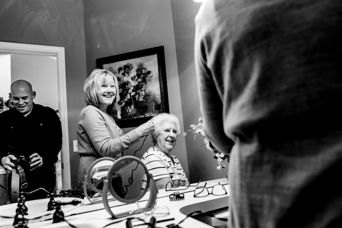 A candid black and white picture taken in a mirror of a photographer taking a picture of a bride's mom and sister getting ready.