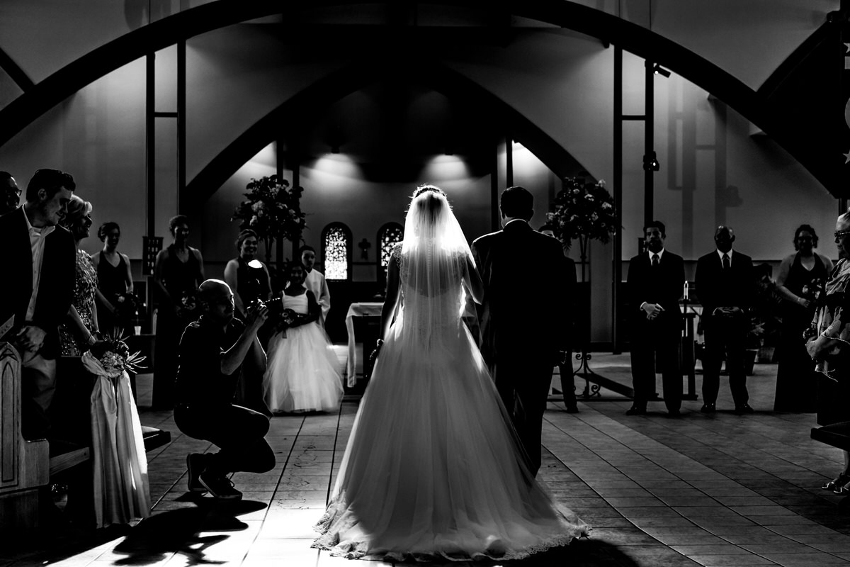 A candid picture taken from behind as a bride and her father are walking into a wedding ceremony, with a photographer seen just off to the side of the bride.