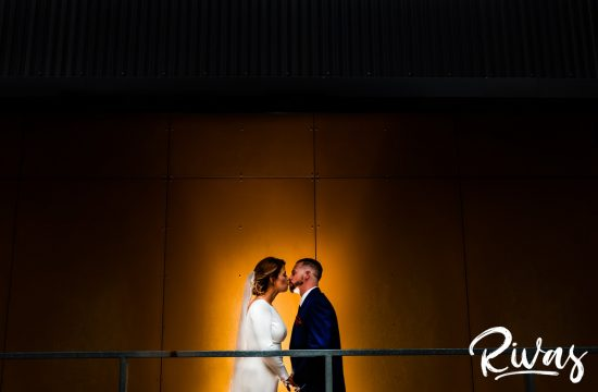 Kansas City Urban Wedding Sneak Peek | A back, spotlit image of a bride and groom standing in front of a deep gold wall sharing a kiss on their wedding day in downtown Kansas City.