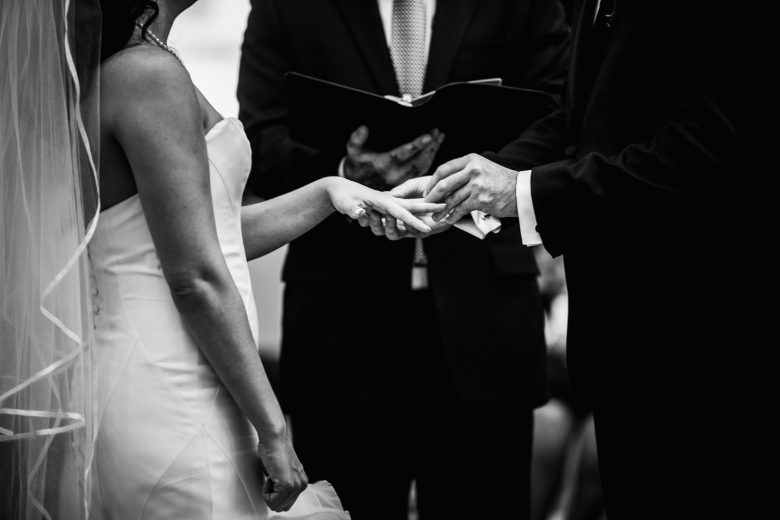 Destination Wedding Photographer | A black and white image of a bride and grom exchanging rings during their wedding ceremony in Kansas City.
