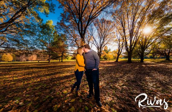Late Fall Engagement Sneak Peek | Rivas | KC Engagement Pictures | A vibrant portrait of an engaged couple standing under a colorful canopy of fall leaves in a grove of trees at Kansas City's Loose Park during their engagement session.