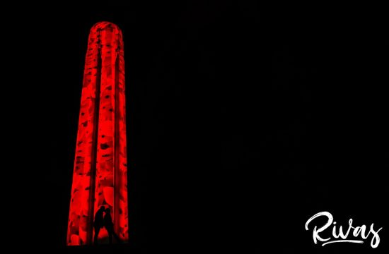 Nighttime Liberty Memorial Engagement Sneak Peek | KC Wedding Photographers | Rivas | A silhouetted portrait of an engaged couple sharing an embrace in front of the pipe at Liberty Memorial, lit up with poppies in remembrance and celebration of the Armistice Centennial Event in Kansas City.