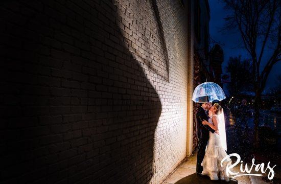 Downtown Lee's Summit Wedding Sneak Peek | A dramatic night time picture of a bride and groom standing next to a cream brick wall underneath a clear umbrella as the rain pours down around them on their wedding day at The Stanley Event Space in downtown Lee's Summit.