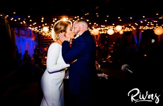 A candid picture of a bride and groom sharing a kiss as they stand on the stage of 28 Event Space during their wedding reception. | Kansas City Room Wedding & Reception | Rivas Weddings
