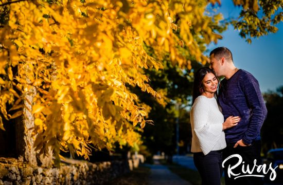 Colorful Nelson Engagement Session | A candid picture of an engaged couple sharing an embrace as they stand in front of a tree with vibrant yellow leaves during their engagement session at The Nelson Atkins Museum of Art in Kansas City.