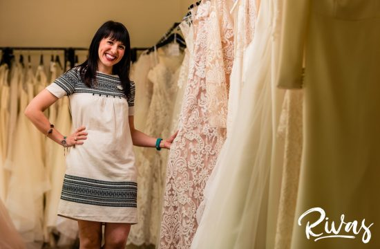 Featured Vendor: Altar Bridal | A candid picture of store manager Sara standing amongst racks of fresh wedding gowns.