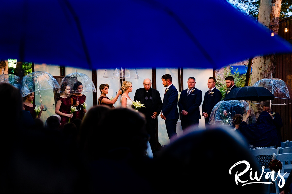 Art Deco Inspired Wedding in Kansas City | A picture taken from under a blue umbrella of a wedding ceremony taking place outside in the rain at Californos.