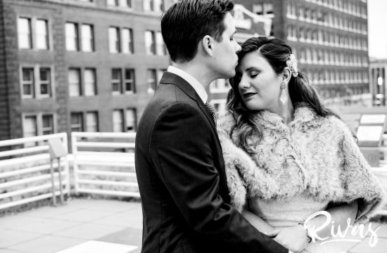 Downtown KC Library Wedding | An intimate black and white picture of a groom kissing his bride on the forehead just after their first look.