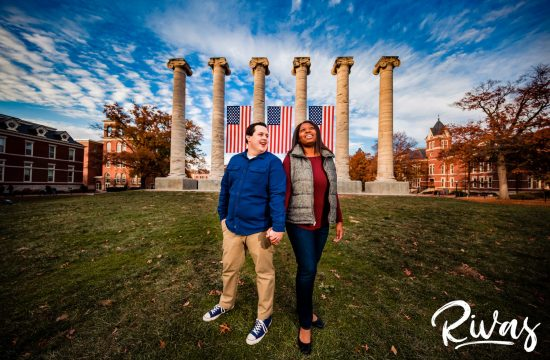 Fall MU Engagement Session | A wide, colorful picture of an engaged couple holding hands while standing in front of the Mizzou columns during their engagement session.