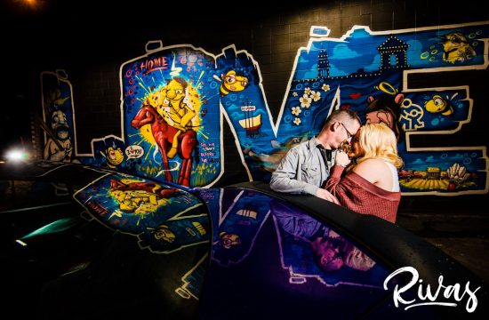 Nighttime Car Engagement Session   A dramatic nighttime portrait of an engaged couple standing back to back and holding hands in front of a pair of purple sports cars, centered in front of a Love Kansas City Mural on Southwest Boulevard.