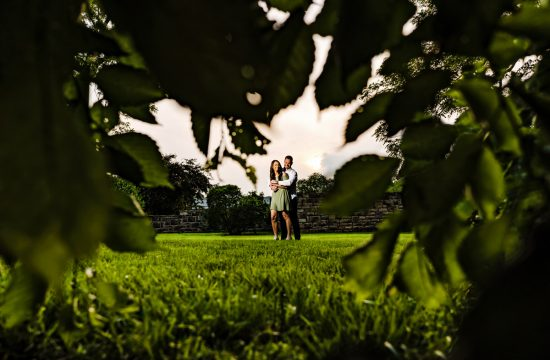 Loose Park Engagement Sneak Peek | A wide picture of an engaged couple sharing an embrace, taken through the tree branches during their engagement session at Loose Park.