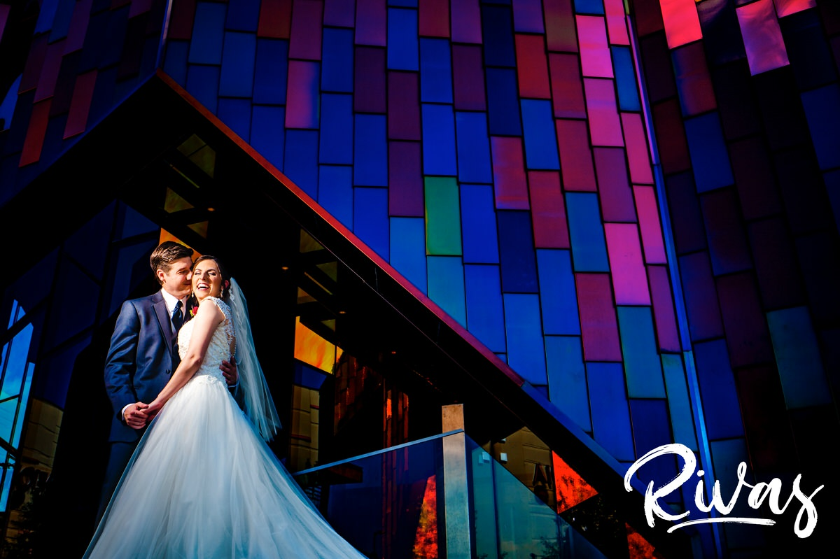 A candid picture of a bride and groom on their wedding day outside the Museum at Prairiefire sharing an embrace and laughing together.