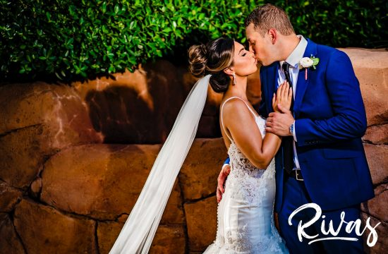 A colorful picture of a bride and groom standing in front of red rocks and greenery embracing and sharing a kiss on their wedding day in Sunny Isles Beach, Florida.