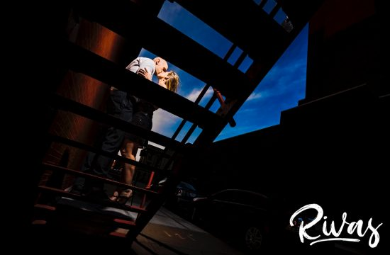 A bright, candid picture of an engaged couple standing on a grated staircase sharing an embrace and kiss during their summer engagement session in downtown Kansas City.