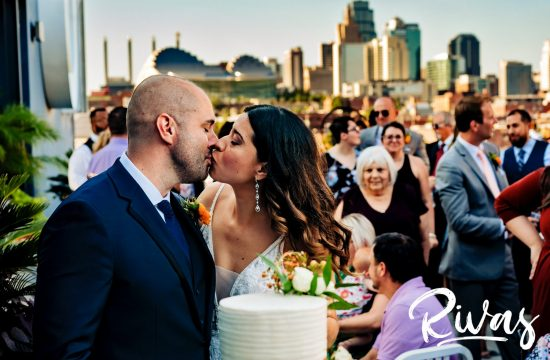 A colorful, candid picture of a bride and groom sharing a kiss as they cut their wedding cake in front of the Kansas City Skyline on their wedding day.