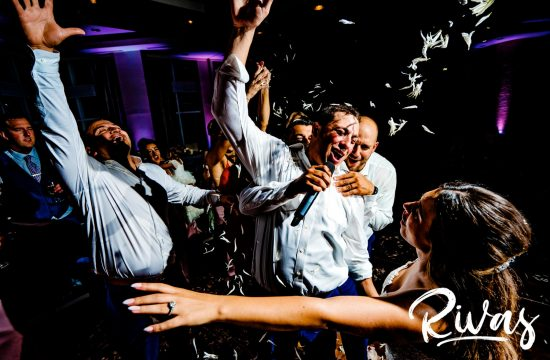A candid picture of a groom singing to his bride as he's surrounded by his groomsmen, flower petals flying through the air, at the end of their wedding reception in Sunny Isles Beach.
