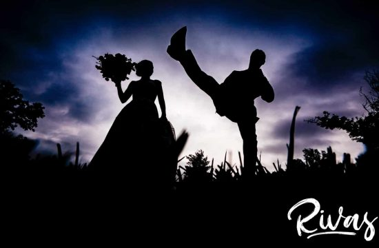 A silhouetted picture of a groom kicking his leg high into the air as his bride watches on their wedding day at The Bowery Event Space.