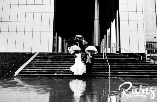 A candid black and white picture of a bride and groom with clear umbrellas running down a set of stairs at The Kansas City Convention Center in the rain on their December wedding day in Kansas City.
