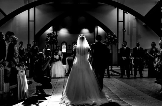 A candid, black and white picture of a bride and her father walking down the aisle with a photographer on the side taking a picture of them during a summer wedding ceremony in Kansas City.