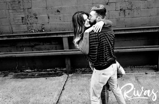 A candid, black and white picture of an engaged couple laughing and sharing an embrace together in Kansas City's West Bottoms neighborhood during their winter engagement session.