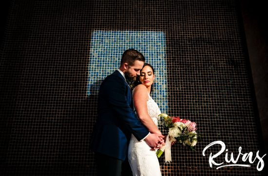 A bold, colorful picture of a modern bride and groom sharing an embrace up against a blue tiled wall bathed in a bright spot of sunlight during their winter wedding day in Kansas City.