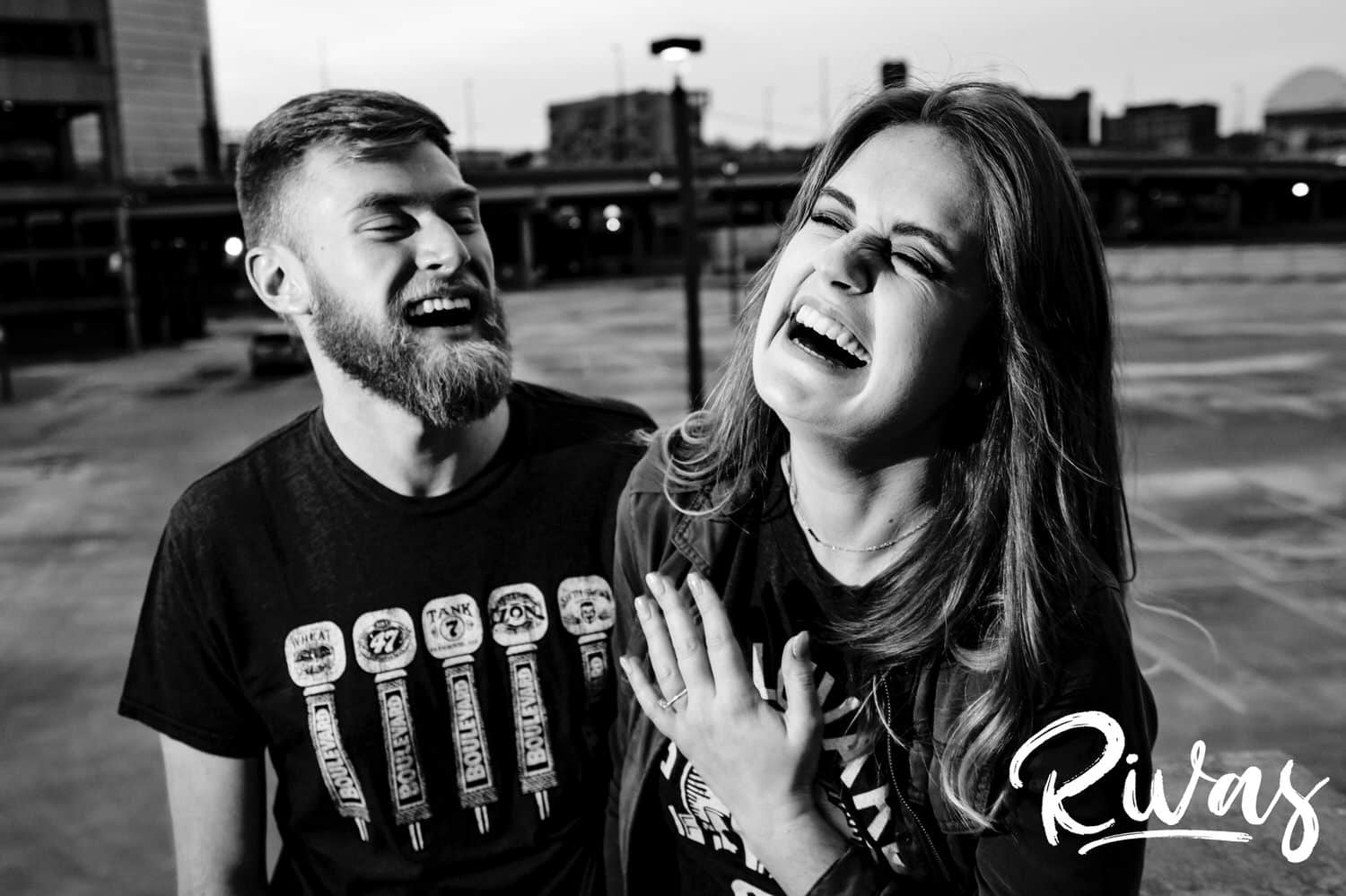 A candid black and white picture of an engaged couple hysterically laughing together during their downtown Kansas City engagement session.