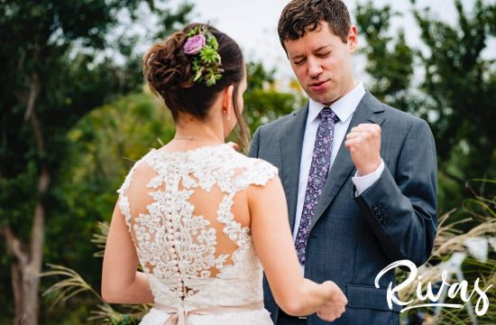 A colorful, candid picture of a groom reacting to seeing his bride for the first time during their first look on their rainy wedding day at The Bowery in Kansas City.