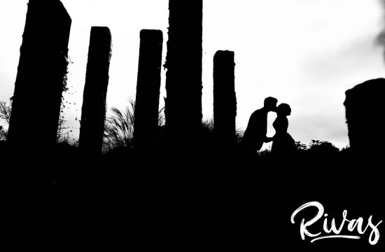 A bold black and white silhouetted image taken through some reeds of a bride and groom sharing a kiss on their rainy wedding day at The Bowery in Kansas City.