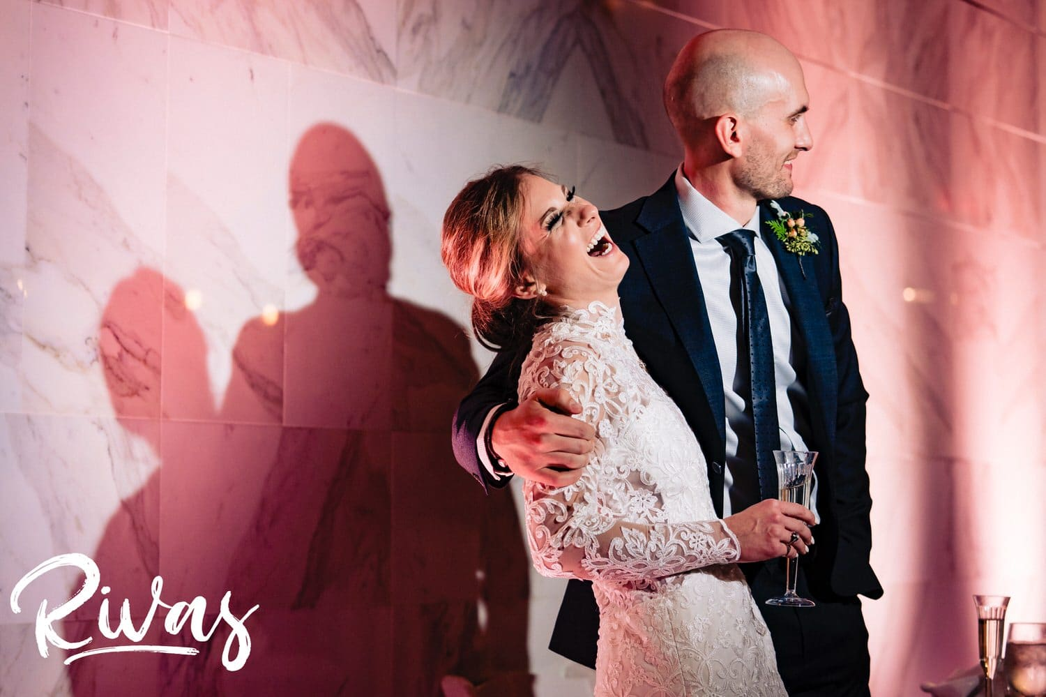 A candid, colorful picture of a bride and groom sharing an embrace and laughing hysterically during the toasts at their winter wedding reception at The Station at 28 Event Space.