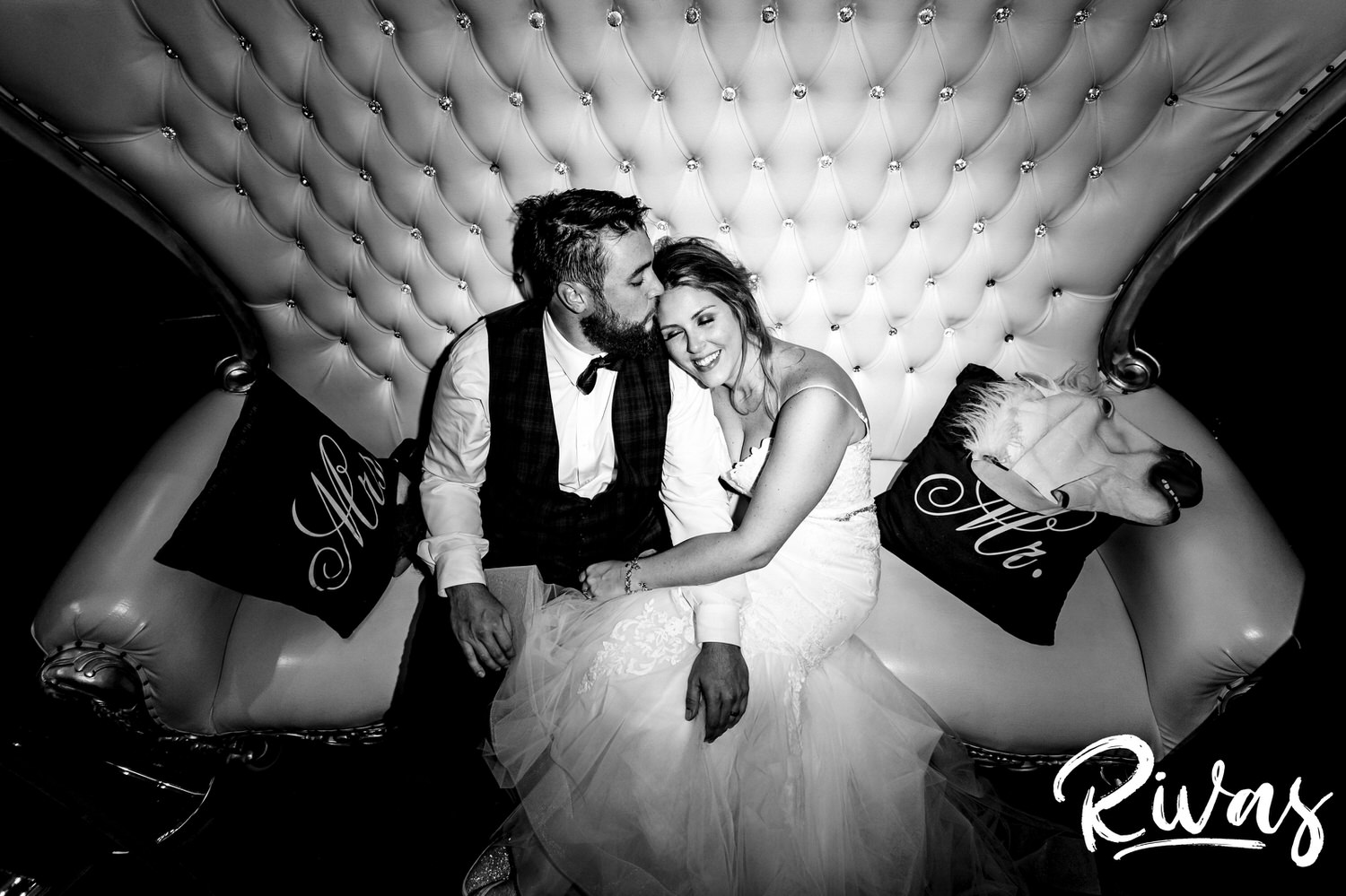A candid black and white picture of a bride and groom collapsed on a large, tufted sofa during their epic reception at Executive Hills Polo Club.