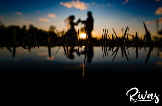 A silhouette of a bride and groom holding hands as the bride's veil blows in the air at sunset, with their reflection visible in the botttom of the frame during their fall wedding day at Piazza Messina in Cottleville, MO.