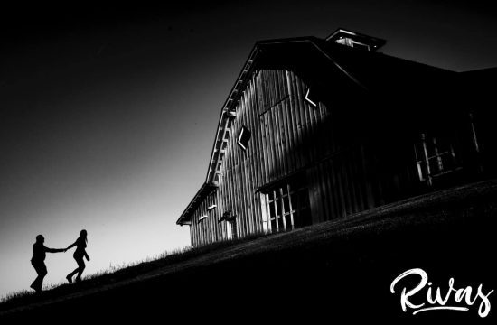 A far-off, black and white picture of a woman leading her fiance up a steep hill towards a giant barn at sunset during the KC engagement session at Schwinn Produce Farm.