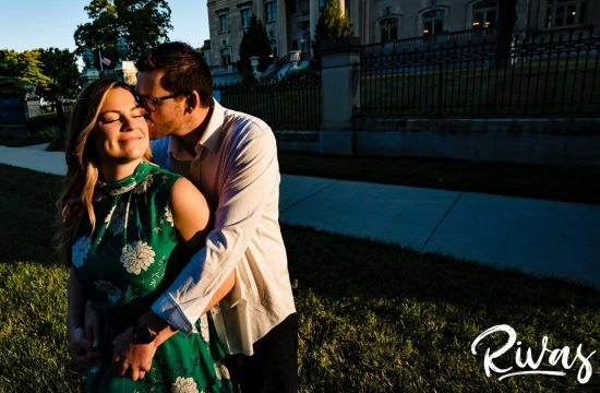 A warm, candid, intimate photo of a man embracing his fiance from behind as he kisses her on the cheek during their summer sunrise engagement session outside the Kansas City Museum.