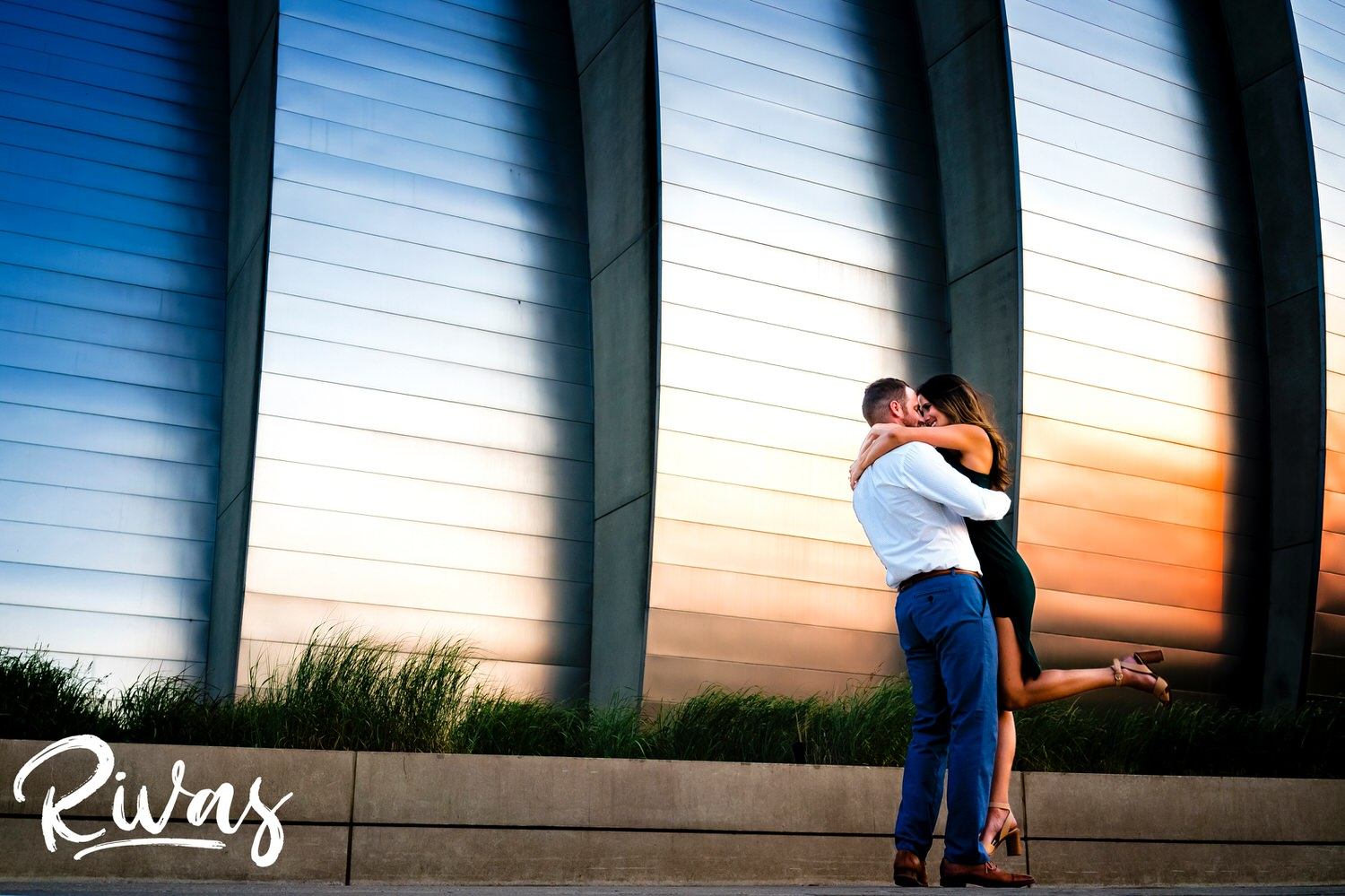 A genuine, carefree, candid engagement picture taken at sunset at the Kauffman Center for the Performing Arts during a summer engagement session in Kansas City.