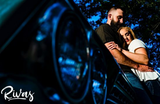 A vibrant portrait of an engaged couple sharing an intimate embrace as they lean up against the fender of an old Impala during their summer engagement session in Kansas City.