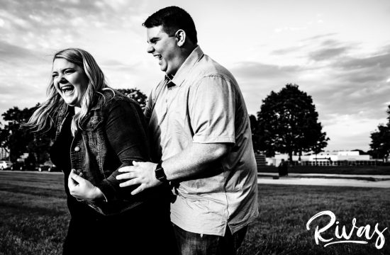 A candid black and white picture of a man tickling his fiance as she laughs hysterically and tries to scoot away during their Liberty Memorial summer engagement photography session in Kansas City.