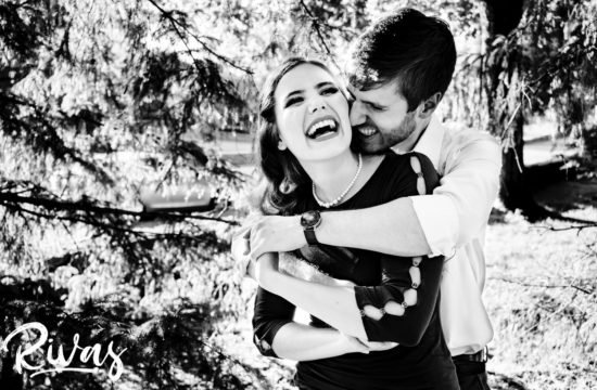 A candid black and white picture of a man hugging his fiance as she laughs hysterically during their summer engagement session at The Nelson Atkins Museum of Art in Kansas City.