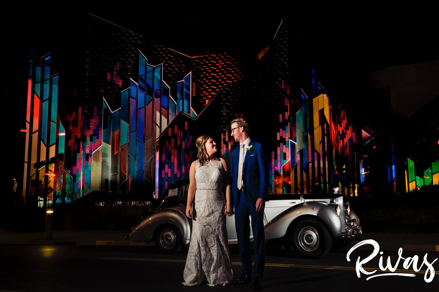 A vibrant picture of a bride and groom holding hands and looking at each other as they stand in front of an antique Bentley parked in front of the Museum at Prairiefire on their wedding night in Kansas City.