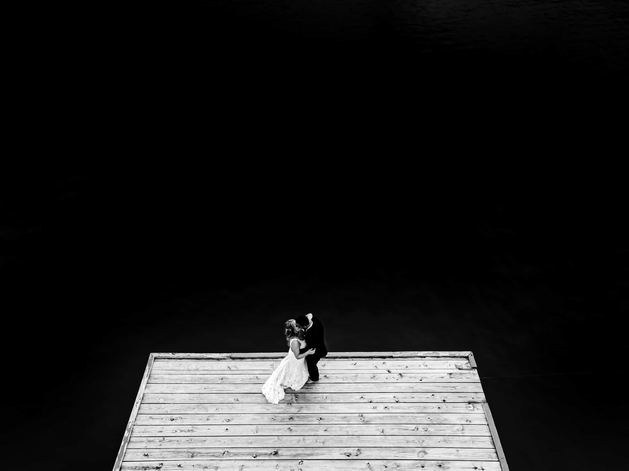A dramatic black and white portrait of a bride and groom standing on a dock, sharing a kiss on their Kansas City Wedding Day.
