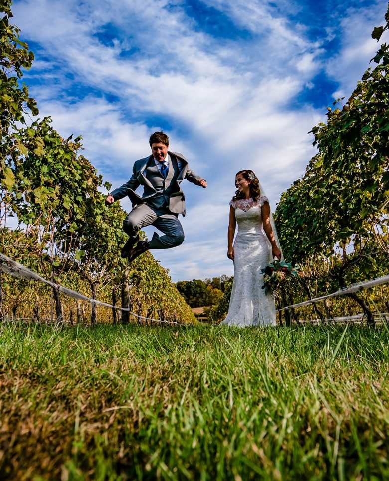 A colorful, candid picture of a groom jumping up into the air and clicking his heels together as his bride watches, laughing.