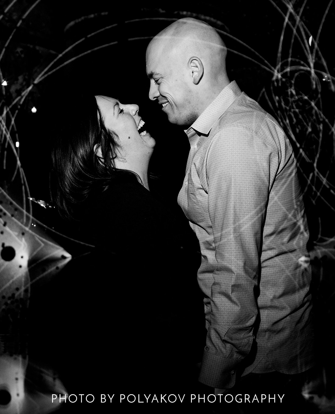 A candid black and white picture of a man and woman holding hands and laughing hysterically as the look at each other.