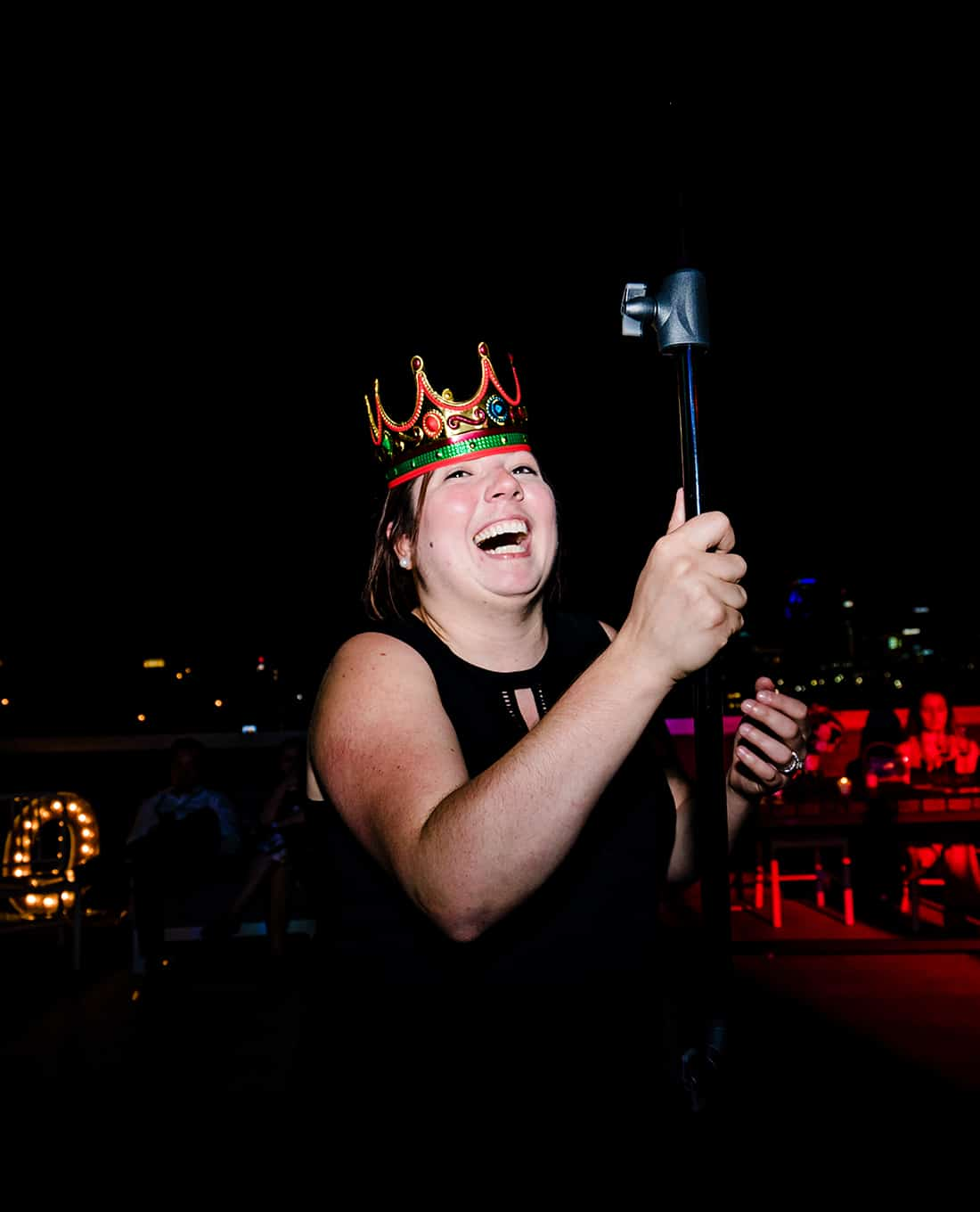A colorfl, candid picture taken at night of a photographer holding a lightstand in the middle of a dance floor with a plastic crown on her head, laughing hysterically.
