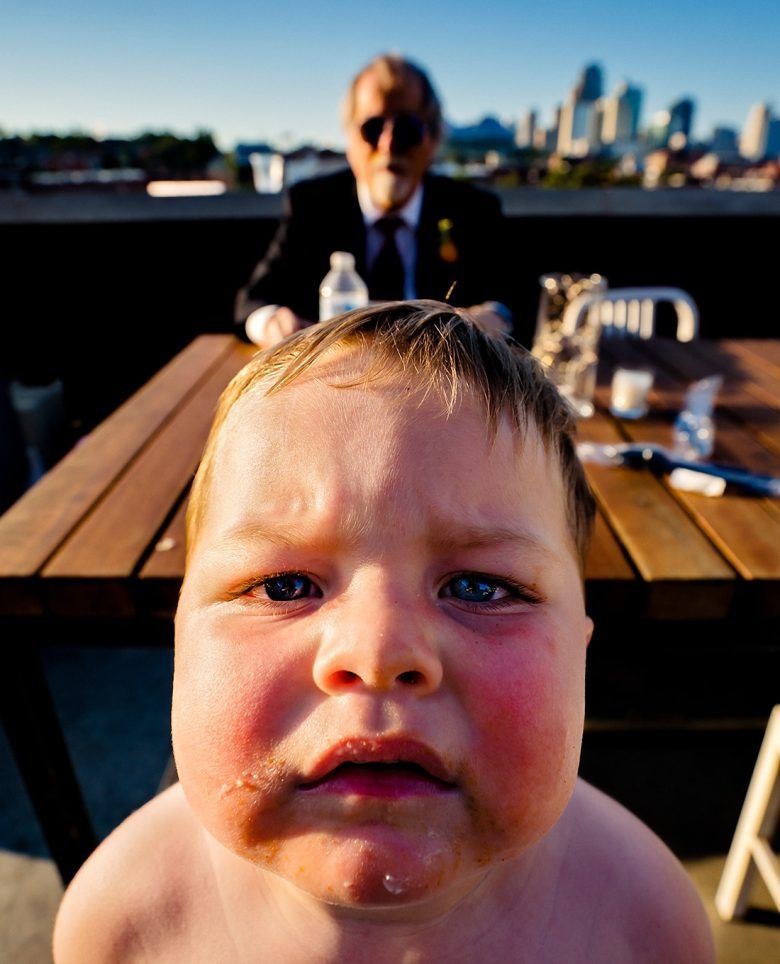 A close-up, candid picture of a shirtless ring bearer staring fixatedly into the camera as a man in sunglasses eats cake in the background.