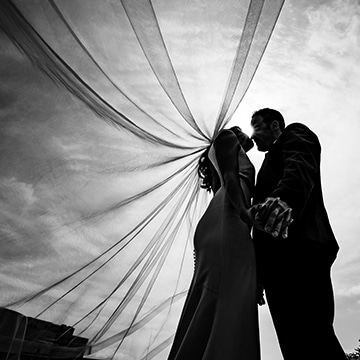 A center-focused, black and white picture of a bride and groom, silhouetted, standing in the center of the frame underneath a bright sunny sky with the bride's veil blowing in the wind around the couple on their summer wedding day at The Otten on Main.
