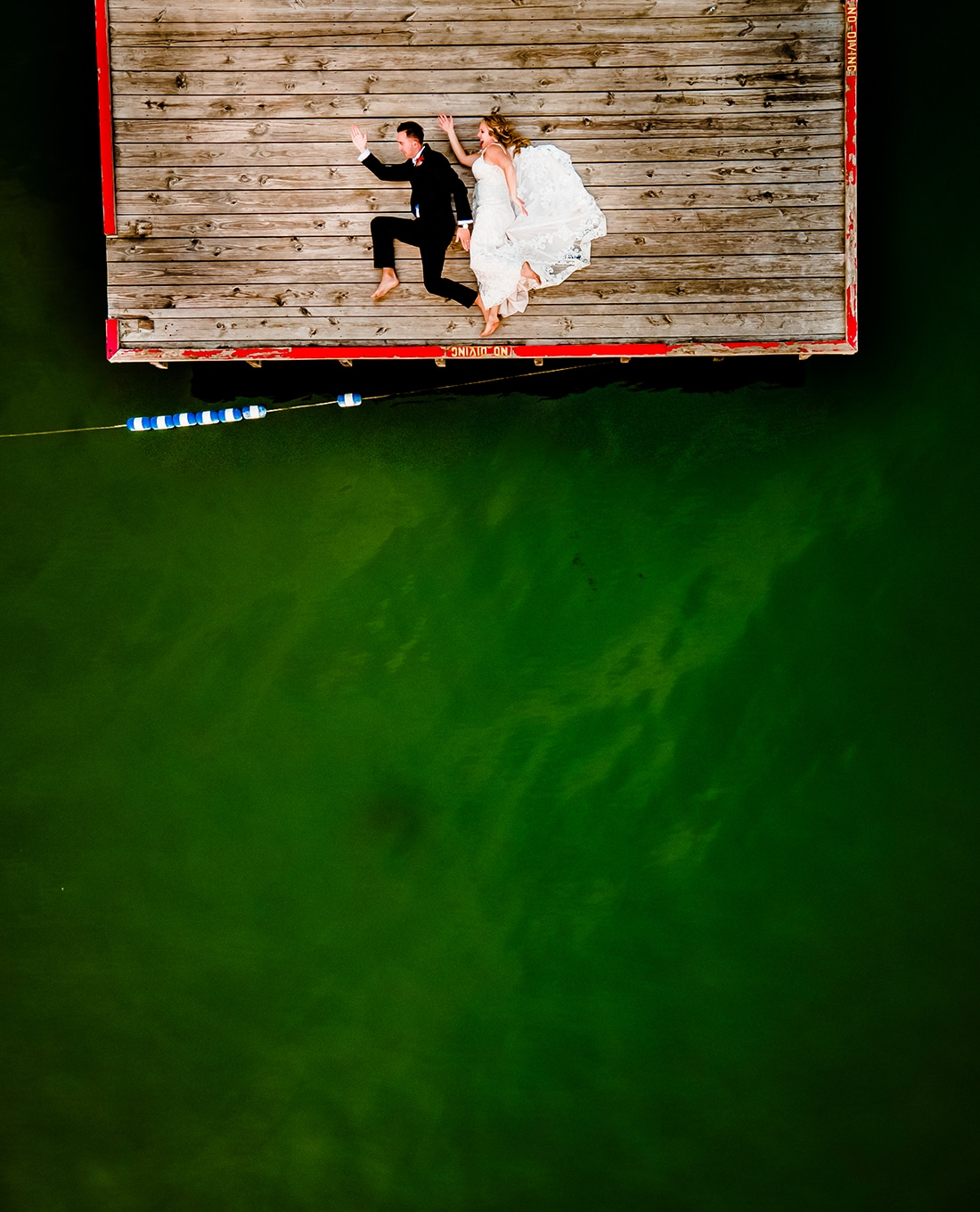 A colorful picture taken from above of a bride and groom, laying outstreetched on a dock as if they are running, green water visible around them on their Kansas City wedding day at Lake Quivira Country Club.