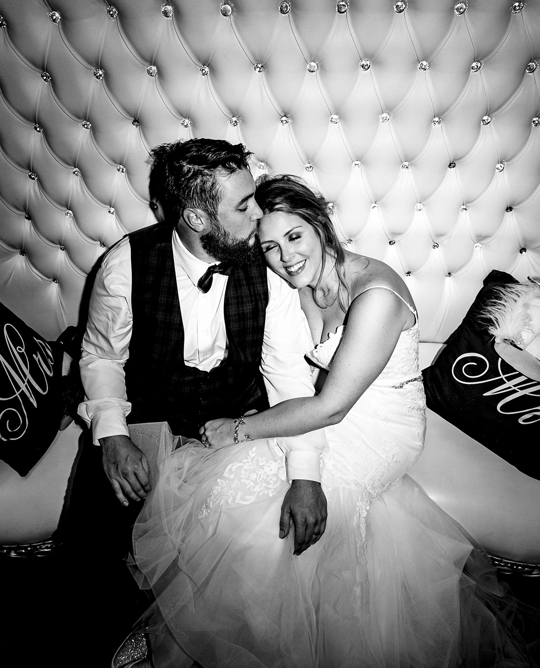 A casual, candid black and white picture of a bride and groom, snuggled on an elaborate couch, the groom kissing the bride on her forehead at the end of their wedding reception in Kansas City