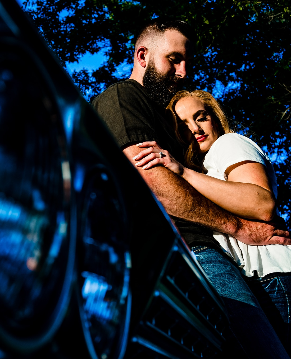 A colorful portrait of an engaged couple sharing an embrace as the lean up against the hood of a vintage Impala during their Kansas City Engagement Session.